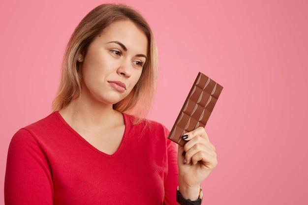Photo d'une femme sérieuse avec une barre de chocolat au cacao