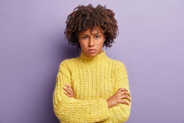 Photo d'une femme sérieuse confiante avec des cheveux afro, garde les bras croisés, regarde avec colère la caméra