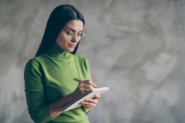 Photo de femme sérieuse confiante en notant les informations entendues par l'employé tenant un cahier d'écriture avec un stylo isolé fond de couleur gris béton