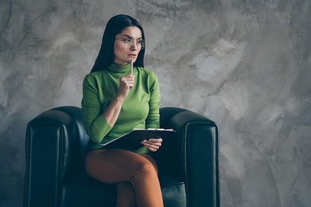Photo de femme sérieuse confiante en pantalon orange touchant le menton avec un stylo tenant le presse-papiers à la recherche dans l'espace vide rêveusement dans des lunettes mur gris isolé fond de couleur béton