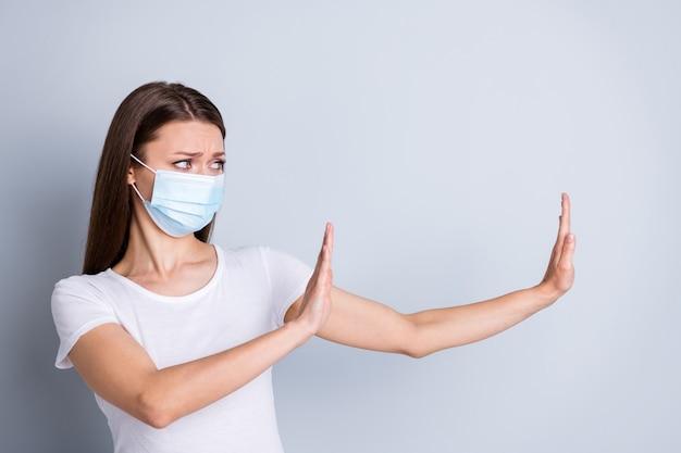 Photo d'une femme sérieuse garder la distance sociale éviter les contacts avec les gens lever les bras côté espace vide