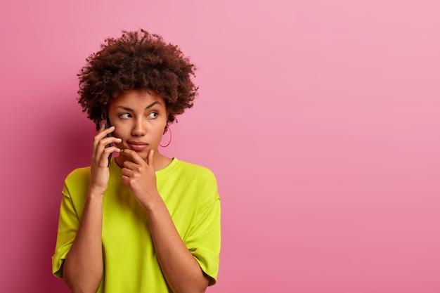 Photo d'une femme sérieuse à la peau sombre tient le menton, a une conversation téléphonique, vêtue de vêtements lumineux décontractés, regarde de côté, pose