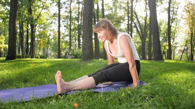 Photo d'une femme souriante d'âge moyen pratiquant le yoga et méditant au parc. femme s'étirant et faisant du fitness sur tapis à forest