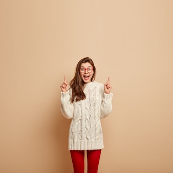 Photo d'une femme souriante avec une expression satisfaite, rit joyeusement, montre quelque chose au-dessus, pointe vers le haut, montre un espace pour le contenu publicitaire, porte un pull blanc tricoté, des lunettes transparentes