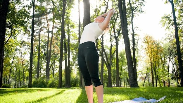 Photo d'une femme souriante faisant des exercices de yoga et de remise en forme. personnes d'âge moyen prenant soin de leur santé. harmonie du corps et de l'esprit dans la nature