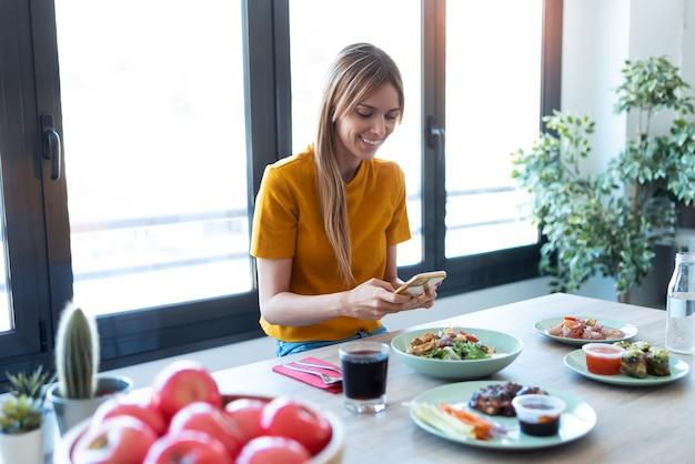 Photo d'une femme souriante mangeant des aliments sains tout en utilisant son téléphone portable à la maison.