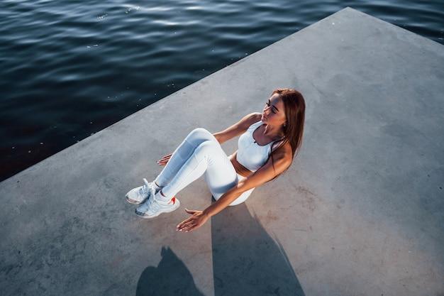 Photo d'une femme sportive faisant des exercices de fitness près du lac pendant la journée
