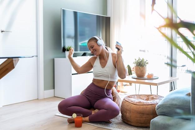 Photo d'une femme sportive et heureuse s'amusant à faire de l'exercice tout en écoutant de la musique avec des écouteurs dans le salon à la maison.