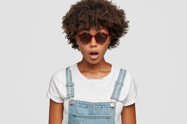 Photo d'une femme surprise à la peau foncée avec une coiffure afro, garde la bouche ouverte, réagit à de fausses nouvelles soudaines