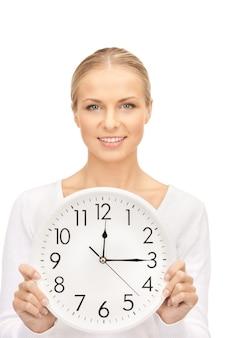 Photo de femme tenant une grosse horloge sur blanc