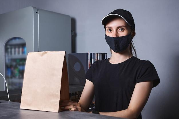 Photo de femme vendeur souriant avec masque debout derrière la caisse enregistreuse