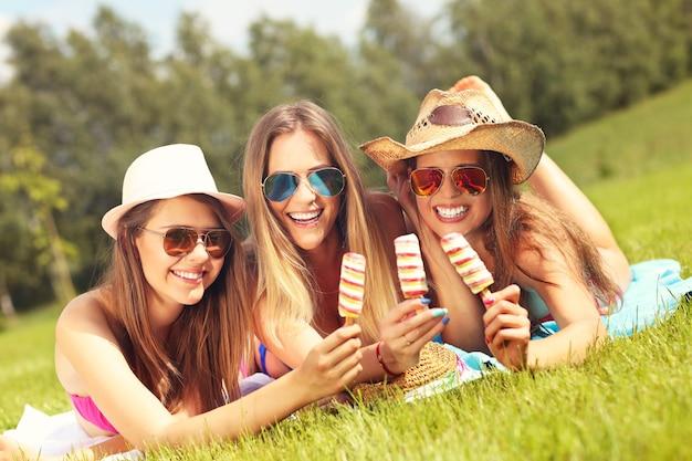 Photo de femmes heureuses se détendre avec une glace à l'extérieur