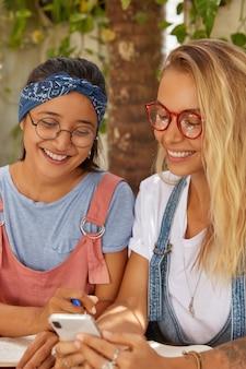 Photo de femmes métisses heureux regardent avec des expressions joyeuses