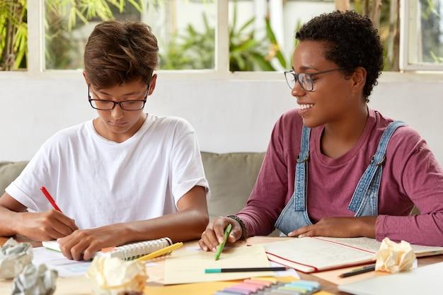 Photo de femmes multiethniques écrivent des notes pour faire du papier de diplôme