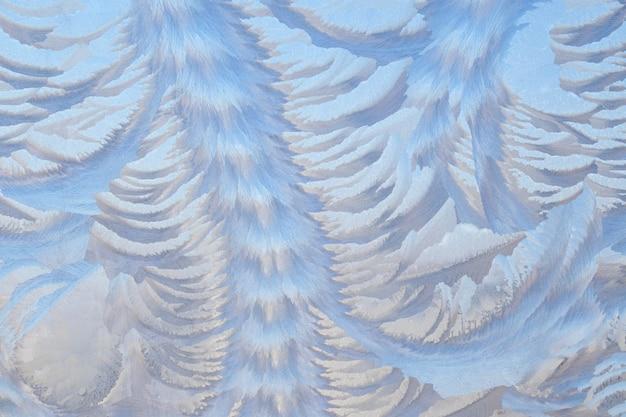 Photo d'une fenêtre gelée. motifs givrés sur le verre. fond de fée d'hiver