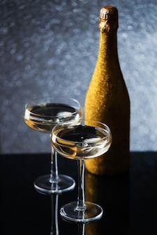 Photo festive de bouteille de champagne dans un emballage d'or avec deux verres à vin