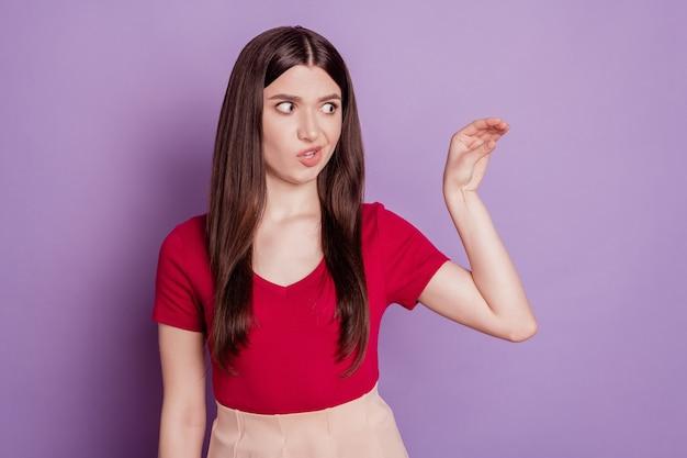 Photo d'une fille agressive en colère regarde l'espace vide simuler la main montrer parler plus de signe sur fond violet