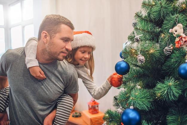 Photo d'une fille assise sur le dos de son père et décorant un arbre de noël avec des jouets.