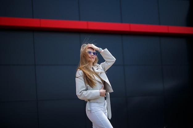 La photo d'une fille aux cheveux longs vêtue d'un chemisier blanc et d'un jean clair se dresse avec un sourire sur le fond du mur gris du bâtiment par une journée de printemps ensoleillée.