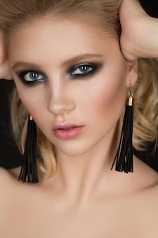 Photo d'une fille blonde avec une peau parfaite sur fond gris.