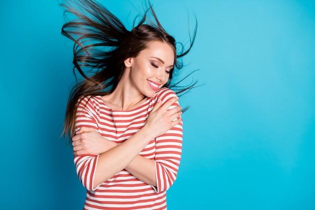 Photo d'une fille candide satisfaite s'embrasser profiter de câlins aimer ses cheveux voler coup de vent isolé sur fond de couleur bleu porter une chemise de bonne humeur