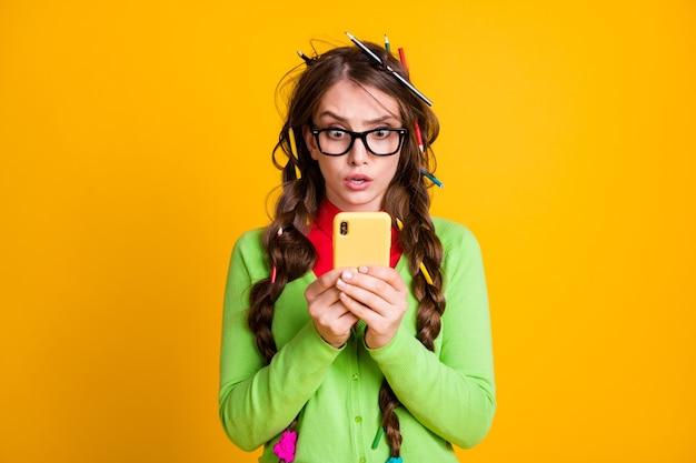 Photo d'une fille confuse avec une coiffure en désordre lire des informations sur un téléphone portable isolé sur fond de couleur