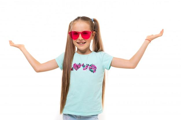 Photo d'une fille avec deux contes de poney, lunettes de soleil roses est souriant isolé sur blanc