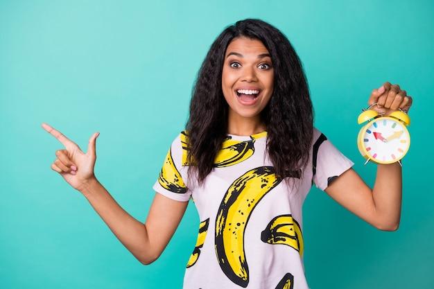 Photo de fille doigt direct espace vide tenir réveil porter un t-shirt imprimé banane fond de couleur turquoise isolé