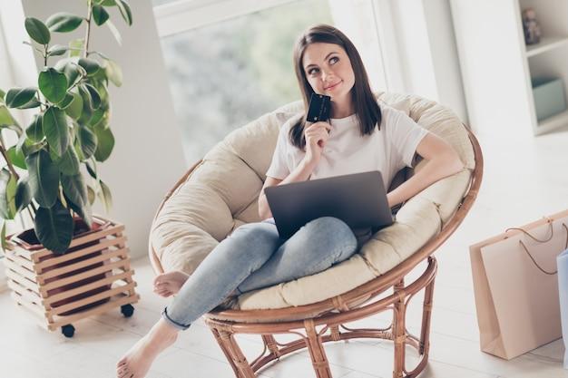 Photo d'une fille d'esprit s'asseoir sur une chaise utiliser un ordinateur portable pour acheter un achat tenir une banque de crédit penser à la maison à l'intérieur
