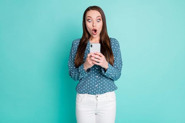 Photo d'une fille étonnée lisant des publications sur les réseaux sociaux sur un téléphone portable, isolée sur fond de couleur turquoise