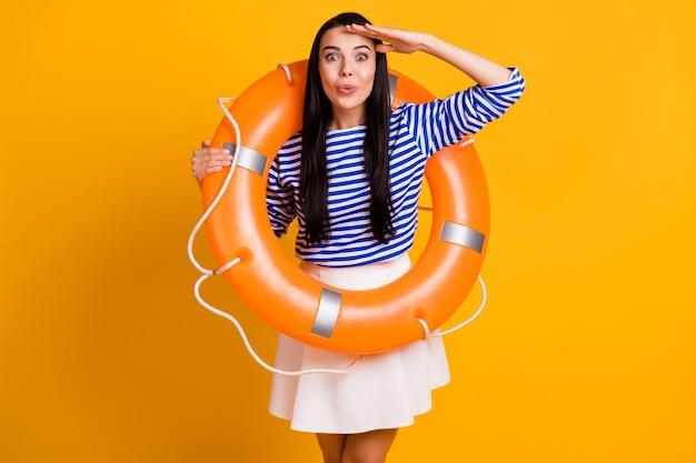 Photo d'une fille étonnée nager touristique avoir une bouée de sauvetage tenir le visage de la main voir la terre de l'eau de l'océan porter une robe jupe chemise blanche bleue à rayures isolée sur fond de couleur brillant brillant