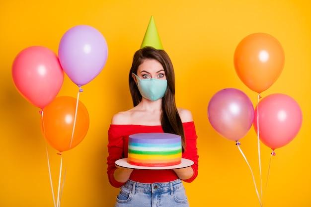 Photo d'une fille étonnée portant un masque médical fêter son anniversaire covid quarantaine tenir le gâteau avoir des ballons porter un cône de jeans en denim haut rouge isolé sur un fond de couleur brillante et brillante