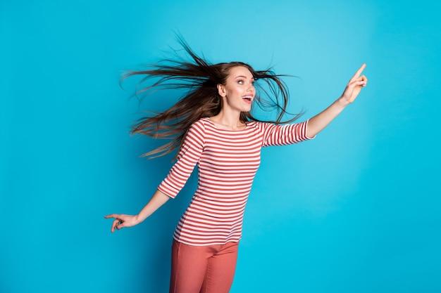Photo d'une fille étonnée voir une publicité incroyable, pointer l'index de la publicité, copyspace sa coiffure, souffler de l'air, porter une tenue élégante à la mode isolée sur fond de couleur bleu