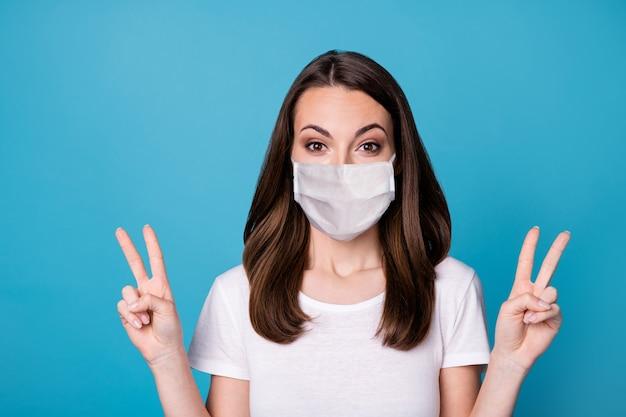 Photo d'une fille excitée étonnée profiter des vacances de week-end de quarantaine covid faire v-sign porter des vêtements de style décontracté masque médical isolé sur fond de couleur bleu