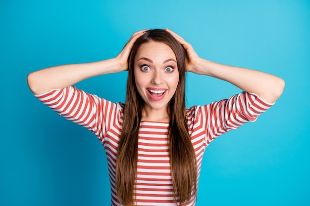 Photo d'une fille folle étonnée entendre une merveilleuse nouveauté de la saison des ventes, impressionner les mains de la tête tactile crier crier porter des vêtements de bonne humeur isolés sur fond de couleur bleu