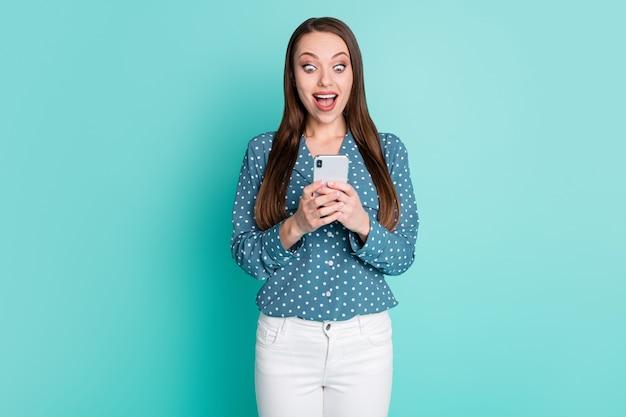 La photo d'une fille folle étonnée a lu d'incroyables nouvelles sur les médias sociaux sur un cri de smartphone isolé sur fond de couleur sarcelle