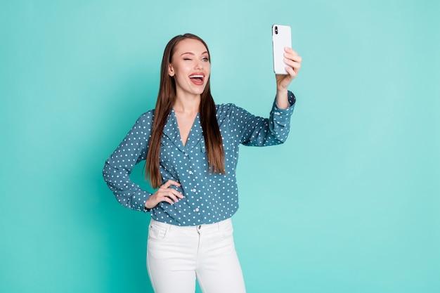 Photo d'une fille folle excitée faire un autoportrait sur un téléphone portable isolé sur fond de couleur pastel sarcelle