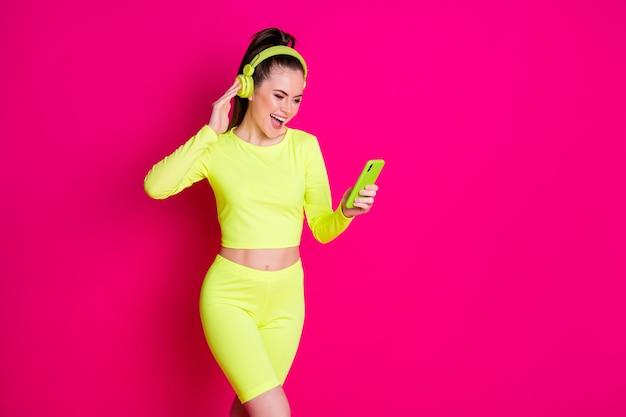 Photo d'une fille folle et mince écouter de la musique de volume de casque utiliser des vêtements de sport pour smartphone isolés sur un fond de couleur rose vif