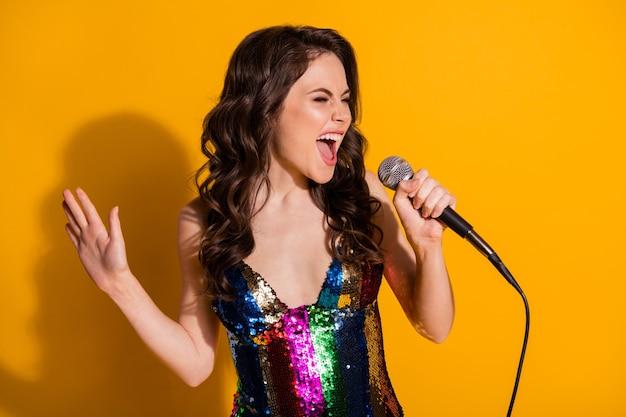 Photo d'une fille folle positive célèbre pop star chanter une chanson utiliser un microphone porter une jupe brillante isolée sur un fond de couleur brillant