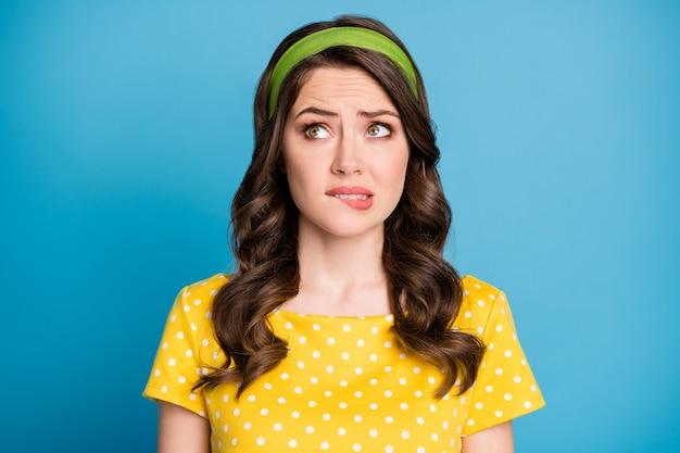 Photo d'une fille frustrée regarde l'espace vide mord les lèvres dents problème de pensée isolé sur fond de couleur bleu