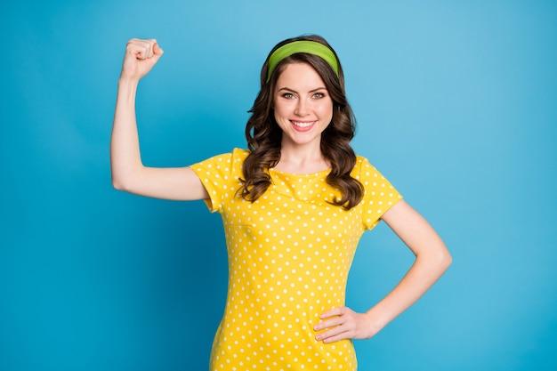 Photo d'une fille gaie positive montre ses muscles de la main porter une tenue à pois isolée sur fond de couleur bleu