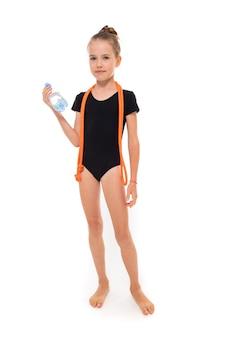 Photo de fille gymnaste en trico noir en pleine hauteur avec une corde à sauter autour du cou et une bouteille d'eau à la main isolé sur fond blanc