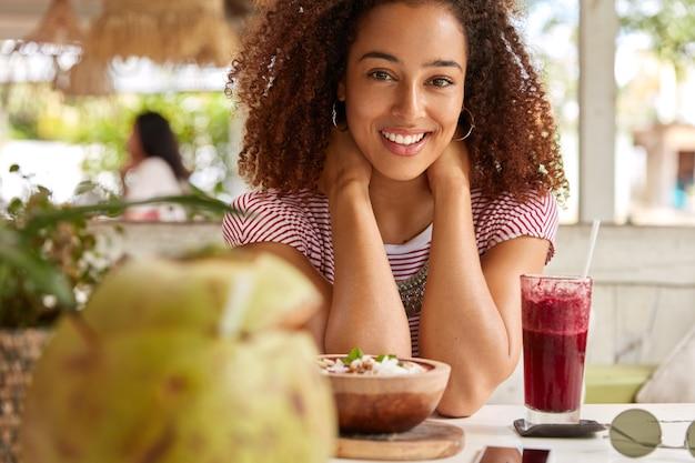 Photo d'une fille heureuse à la peau sombre sourit positivement à la caméra