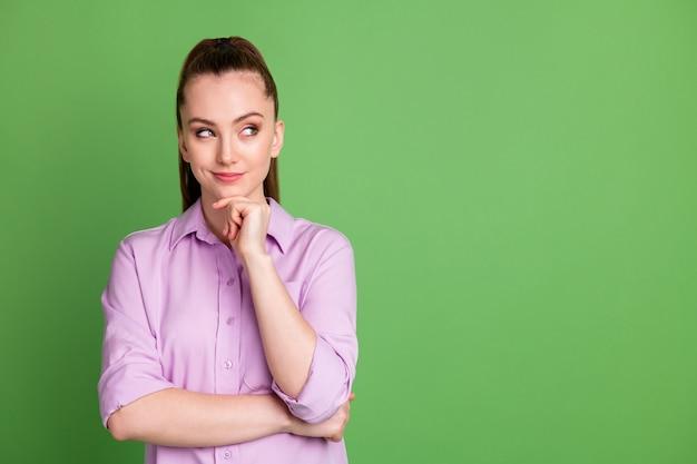 Photo d'une fille intelligente à l'esprit regarder copyspace toucher le menton de la main pense que les pensées décident de choisir le choix de la solution de décision porter une tenue lilas isolée sur fond de couleur verte