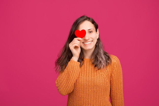 Photo d'une fille joyeuse avec du papier coeur rouge sur les yeux sur l'espace rose