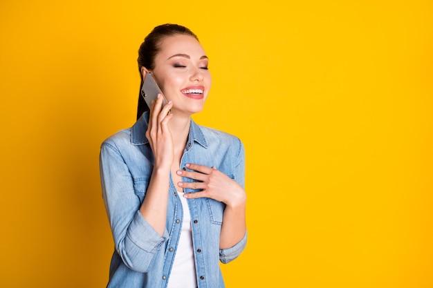 Photo d'une fille joyeuse et positive appeler un téléphone portable écouter son amie plaisanter en riant toucher la poitrine à la main porter un style élégant denim à la mode isolé sur un fond de couleur brillante et brillante