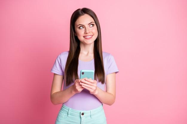 Photo d'une fille joyeuse et positive utiliser un plan de téléphone portable quoi écrire sur les médias sociaux regarder copyspace porter un pantalon turquoise turquoise pantalon violet isolé sur fond de couleur rose