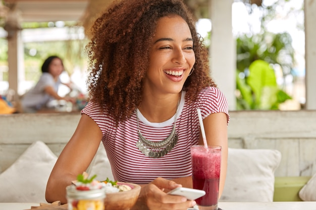 Photo d'une fille à la peau sombre ravie a les cheveux touffus, rit et regarde de côté, utilise un téléphone portable pour la communication en ligne et la messagerie avec des amis, boit du smoothie dans une cafétéria confortable