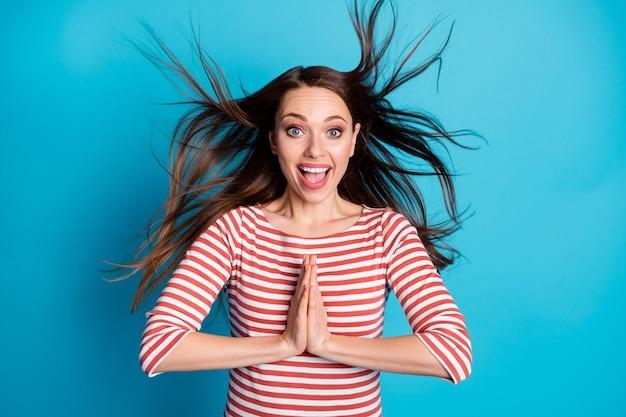 Photo d'une fille positive et étonnée impressionnée par un cadeau chanceux attendu depuis longtemps mettre les mains ensemble crier wow omg porter une belle chemise isolée sur fond de couleur bleu