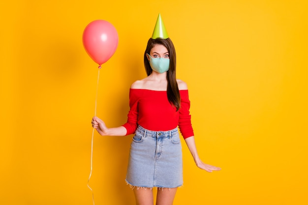 Photo d'une fille positive portant un masque médical profitez de la fête d'anniversaire de quarantaine covid tenir un ballon porter des jeans en denim haut rouge mini jupe cône isolé sur fond de couleur brillant brillant